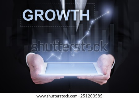 Businessman holding a tablet with growth graph on the screen. business concept - stock photo