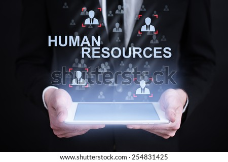businessman holding a tablet with human resources concept on the screen. Internet concept. business concept. - stock photo