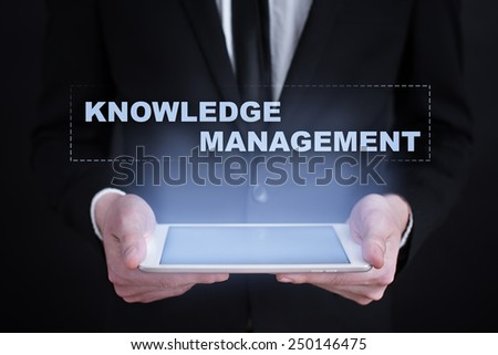 Businessman holding a tablet with knowledge management text on the screen. business and education concept. - stock photo
