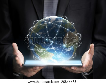 Businessman holding a tablet with planet Earth. Elements of this image furnished by NASA