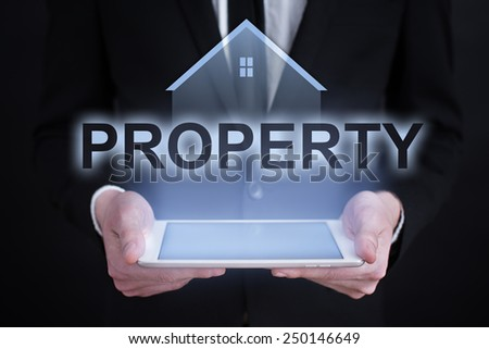 Businessman holding a tablet with property investment concept.  - stock photo