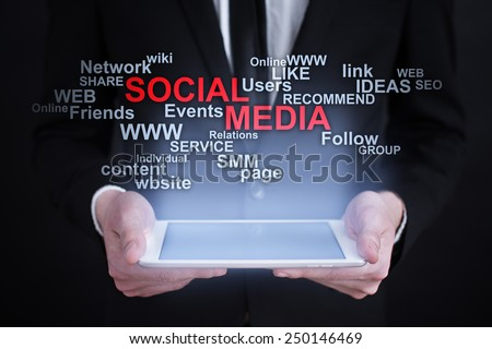 Businessman holding a tablet with social media words cloud on the screen. business  concept. - stock photo