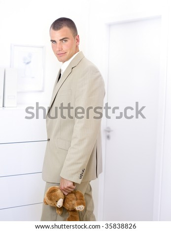 businessman holding a teddy bear