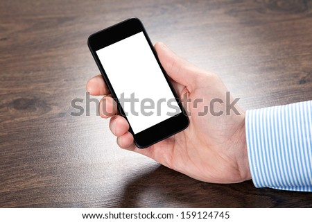 businessman holding a touch phone with isolated screen over the villages table - stock photo