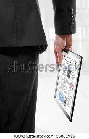 Businessman holding a touchpad pc with an electronic newspaper - stock photo