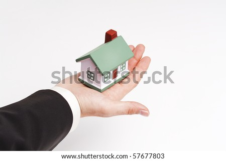 businessman holding a toy house; real estate presentation - stock photo