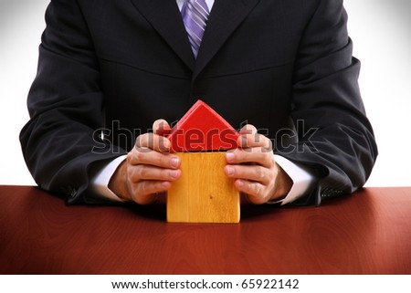 businessman holding a toy house, real estate presentation