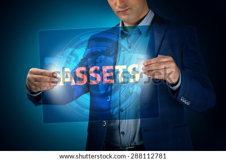 Businessman holding a transparent screen with an inscription a assets. Business, technology, internet and networking concept. - stock photo