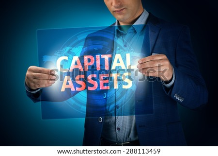 Businessman holding a transparent screen with an inscription a capital assets. Business, technology, internet and networking concept. - stock photo