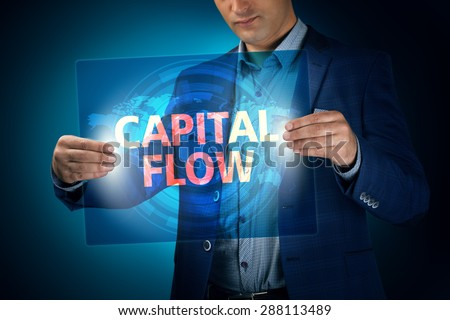 Businessman holding a transparent screen with an inscription a capital flow. Business, technology, internet and networking concept. - stock photo