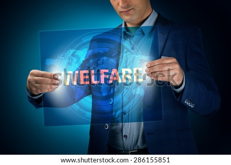 Businessman holding a transparent screen with an inscription a welfare. Business, technology, internet and networking concept. - stock photo