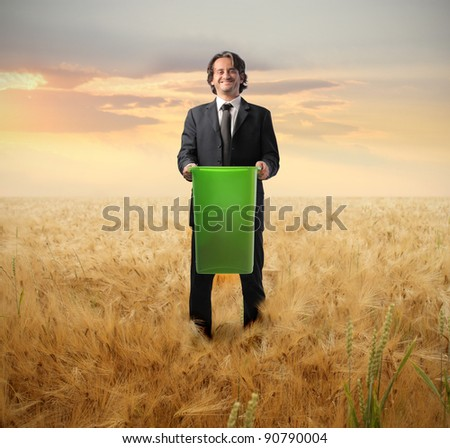Businessman holding a trash bin on a wheat field