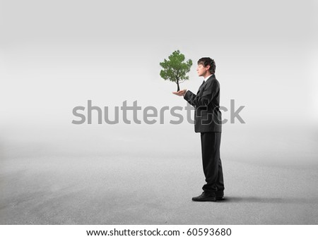 Businessman holding a tree in his hands - stock photo