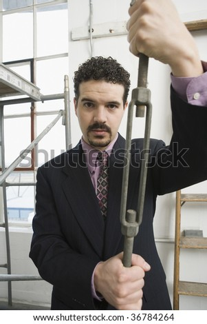 Businessman holding a turnbuckle - stock photo