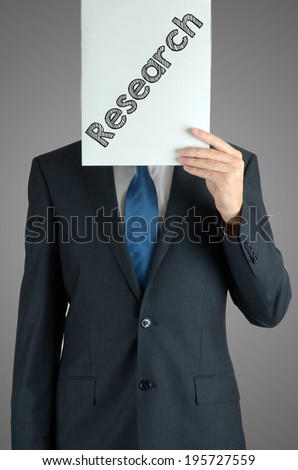 businessman holding a white sheet of paper with the inscription on grey background: research - stock photo