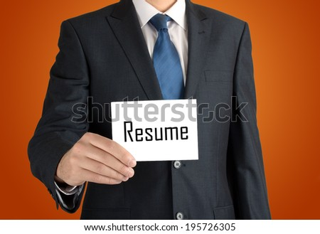 businessman holding a white sheet of paper with the inscription on nice warm orange background: resume - stock photo