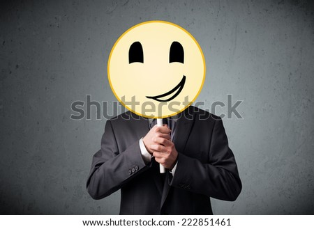 Businessman holding a yellow smiley face emoticon in front of his head - stock photo