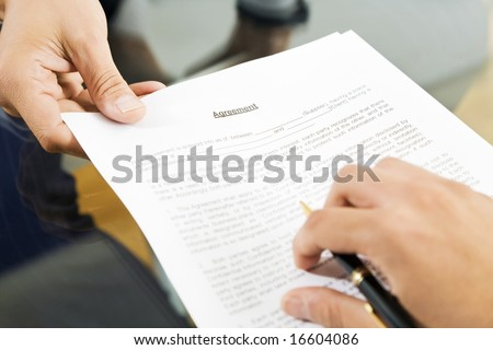 Businessman holding agreement for signature. Close up - stock photo