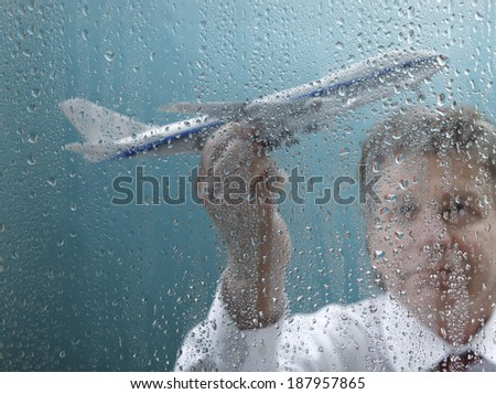 Businessman holding airplane behind wet window - stock photo