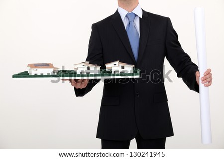 businessman holding an architectural model - stock photo