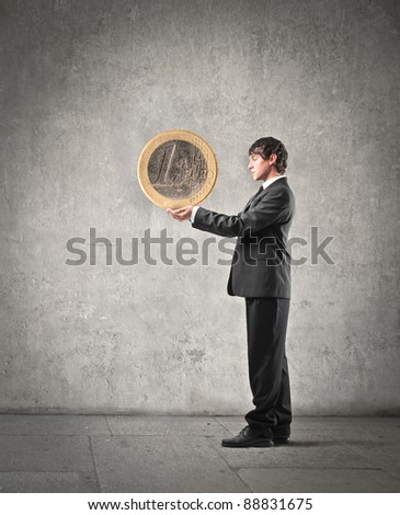 Businessman holding an euro coin - stock photo