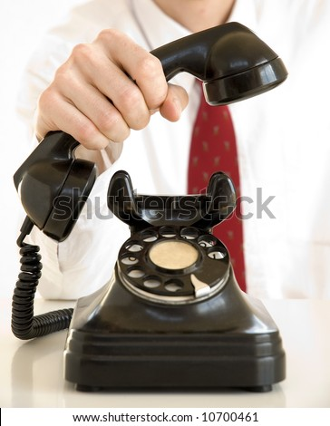 businessman holding an old black telephone