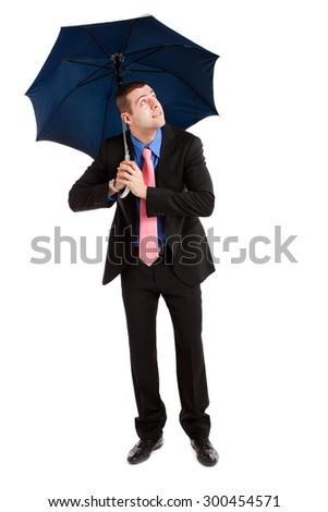 Businessman holding an open umbrella full length - stock photo