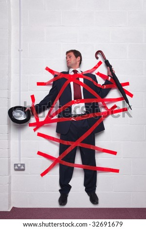 Businessman holding an umbrella and bowler hat stuck to a wall with red tape. - stock photo
