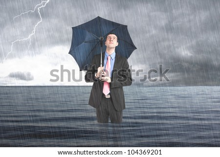 Businessman holding an umbrella in the sea - stock photo