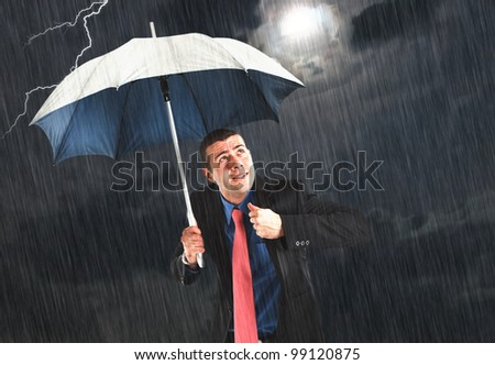 Businessman holding an umbrella in the storm - stock photo
