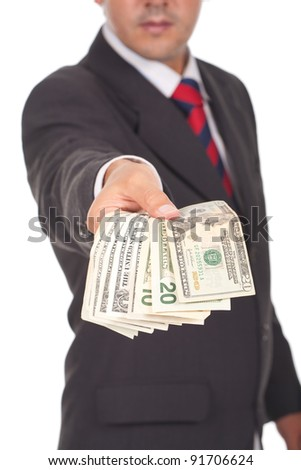 businessman holding and giving away dollar bills (focus is on the hand)