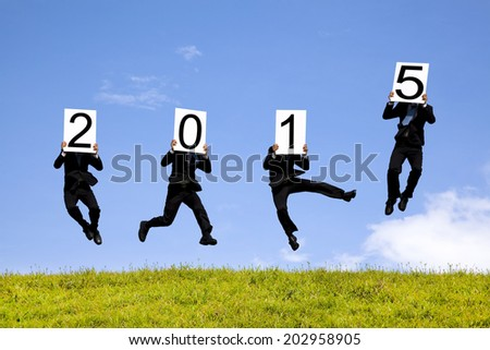 businessman holding 2015 and jumping on a meadow - stock photo