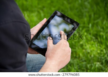 Businessman holding and touching on touch screen digital tablet in the park. Background green grass - stock photo