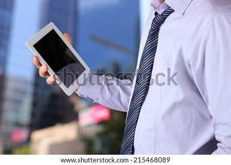 Businessman holding  and using the digital tablet. Modern city behind  - stock photo