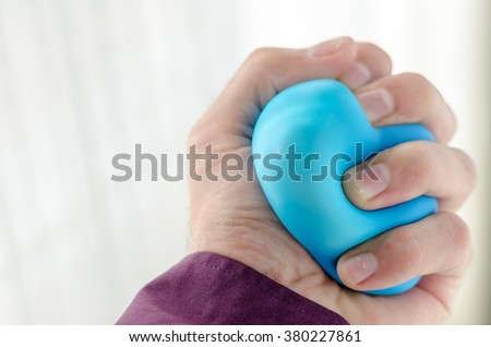 Businessman holding Anti-stress balls in hand, according to the window with bright sunlight - stock photo