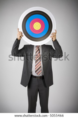 Businessman holding archery target. Covering face. Front view, gray background - stock photo