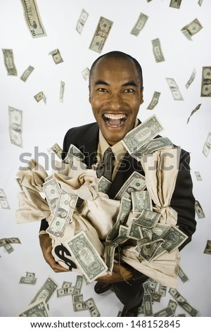 Businessman holding bags of money - stock photo