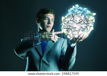 Businessman holding ball of money in hand - stock photo