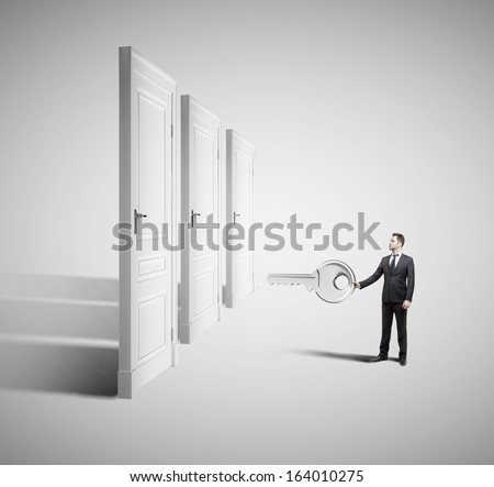 businessman holding big key with closed doors - stock photo