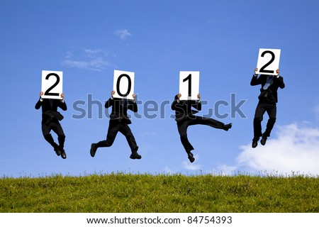 businessman holding 2012 billboard and jumping on the green field - stock photo