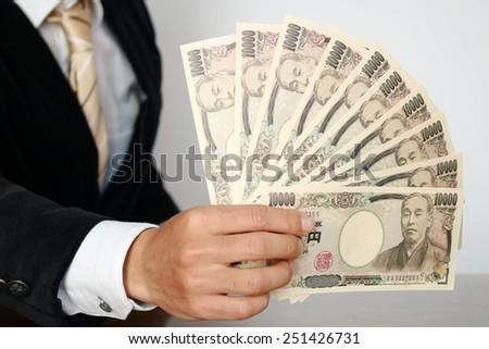 Businessman holding bills - stock photo