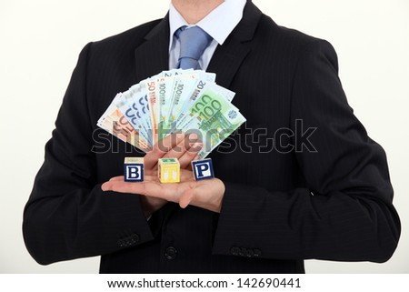Businessman holding bills and toy blocks