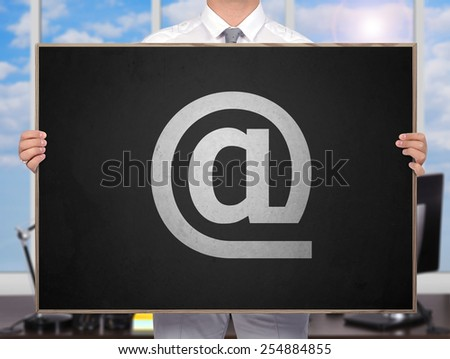 businessman holding blackboard with drawing email symbol - stock photo