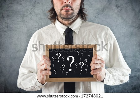 Businessman holding blackboard with question marks. Business questioning.