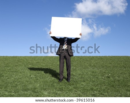 Businessman holding blank board standing in grass. - stock photo