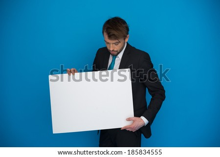 Businessman holding blank poster on blue