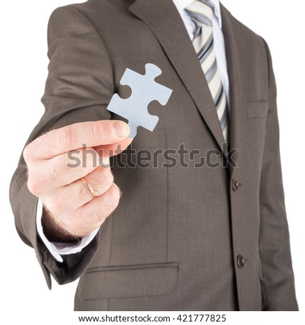 Businessman holding blank puzzle piece towards you isolated on white background