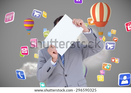 Businessman holding blank sign in front of his head against cloud computing graphic with hot air balloons - stock photo