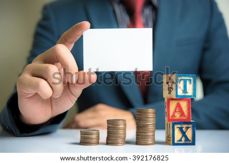 businessman holding blank visit card with Stack Of Coins and TAX word - stock photo