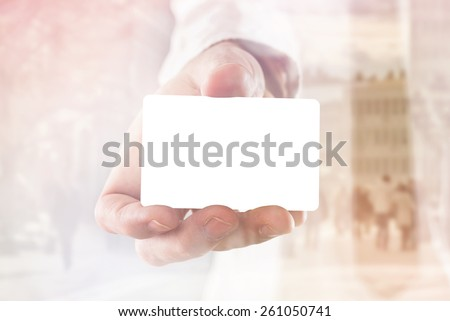 Businessman holding blank visiting card with rounded corners, double exposure image with people on the street, selective focus with shallow depth of field - stock photo